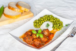 Meatballs in tomato sauce with sauteed peas